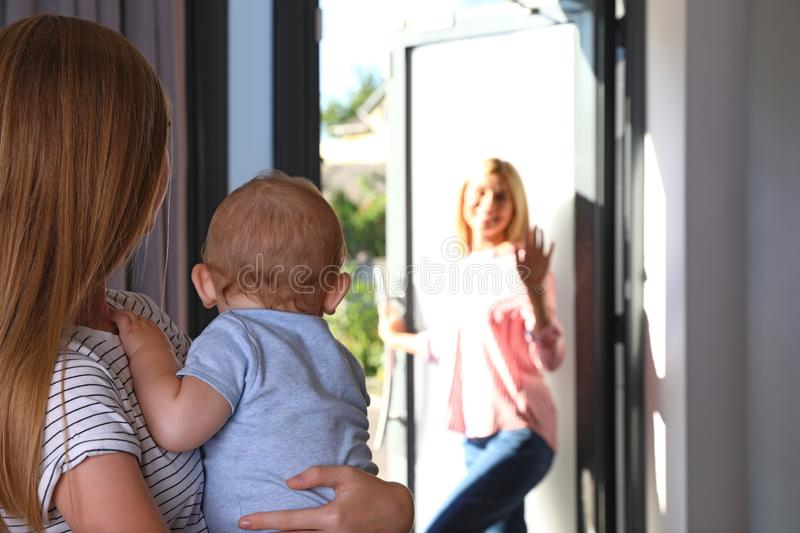 Mother leaving her baby with teen nanny royalty free stock photos