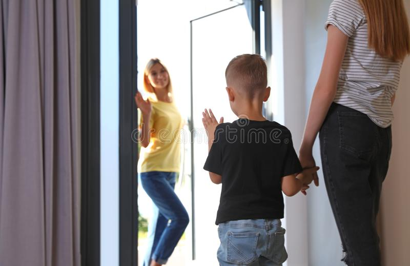 Mother leaving her little son with  nanny at home. Space for text royalty free stock images