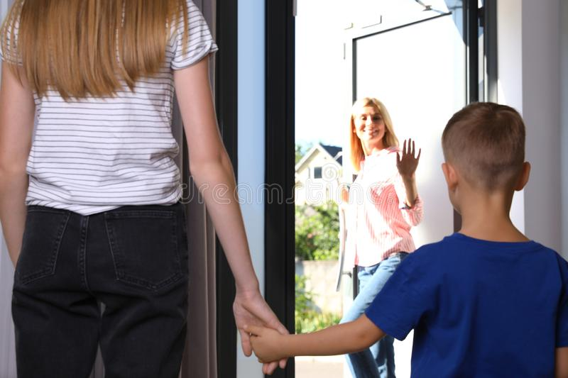Mother leaving her little son with teen  at home stock photos