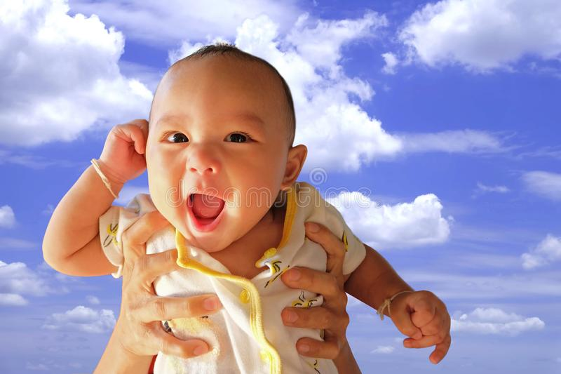 Mother lifting cute Asian baby is carried on the air with have fun laughing smile stock photos