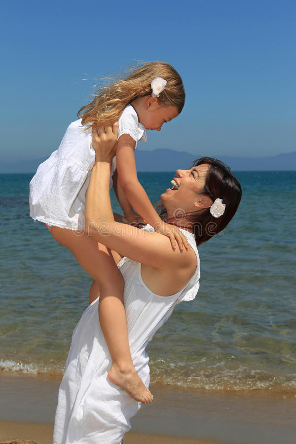Mother lifting daughter up on beach stock image