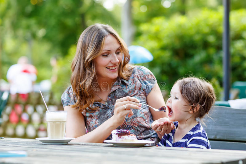 Mother and little adorable kid girl drinking coffee in outdoor c. Young mother relaxing together with her little child, adorable toddler girl, in summer outdoors stock photos