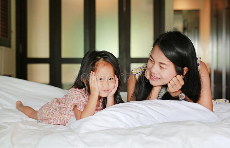 Mother and little asian girl looking camera and lying on bed royalty free stock photo