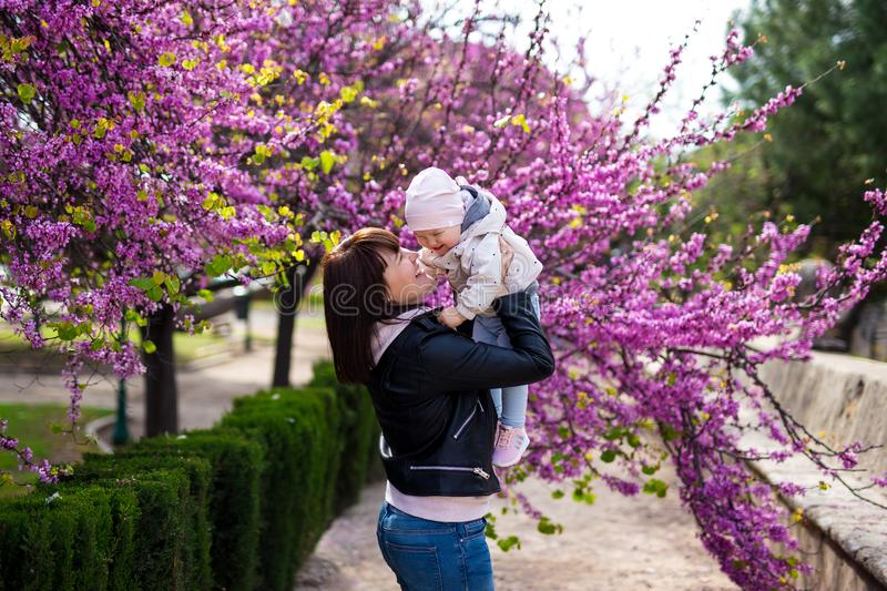 Mother and little baby girl having fun in spring park. Over blooming cherry tree royalty free stock photos