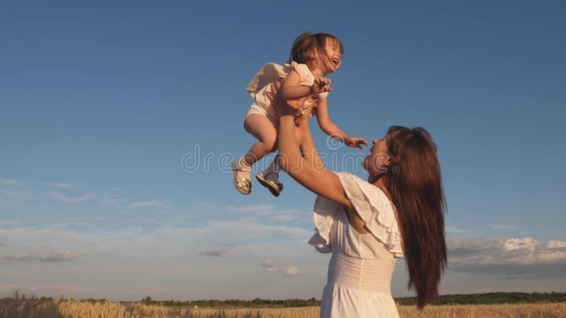 Mother and little baby play on field of ripe wheat. happy family travels. Mom throws up a happy daughter in the sky royalty free stock photography