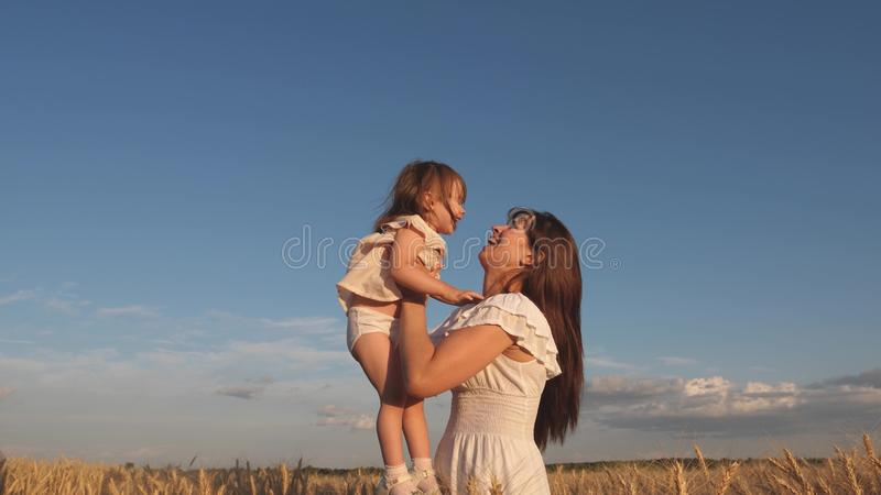 Mother and little baby play on field of ripe wheat. happy family travels. Mom throws up a happy daughter in the sky royalty free stock photo