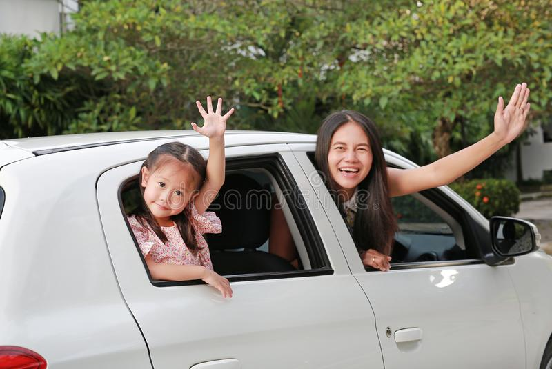 Mother and little child girl sitting on a car looking camera and waving goodbye. Holiday concept royalty free stock photography