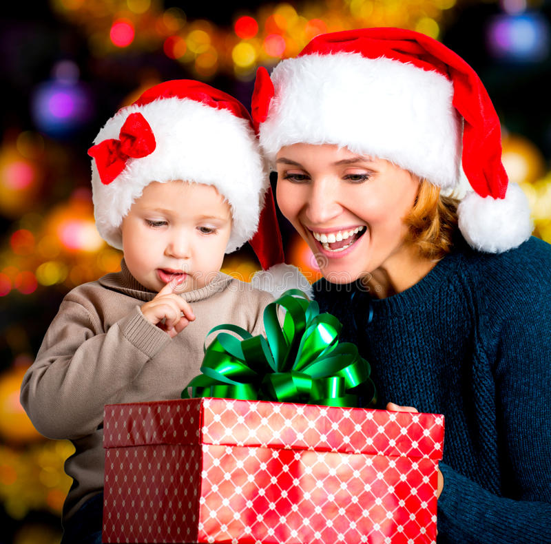 Mother with little child hold box with new year gifts. Smiling mother with little child hold box with new year gifts on the christmas holiday - indoors stock photography