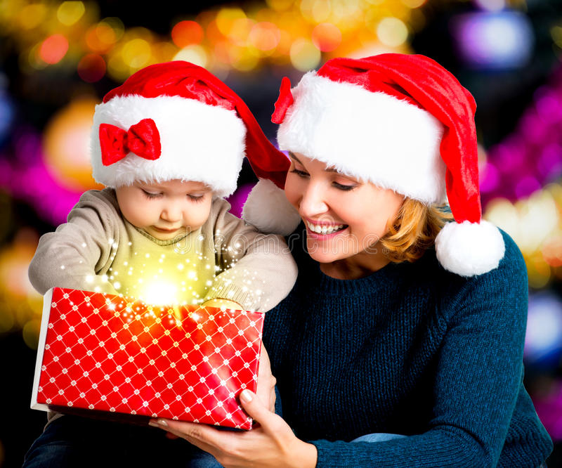 Mother with little child opens the box with gifts on christmas. Mother with little child opens the box with gifts on the christmas holiday - indoors royalty free stock photos
