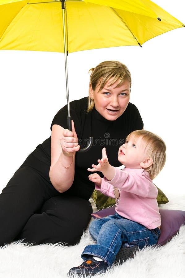 Mother and little child under umbrella