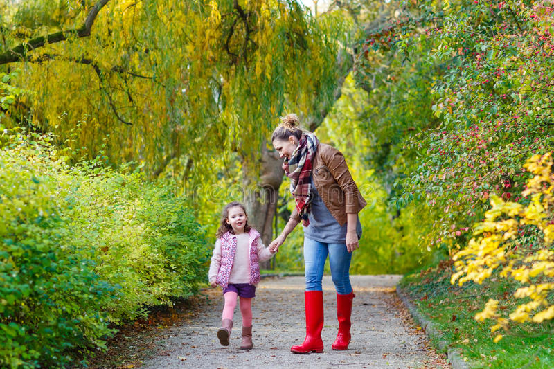 Mother and little daughter at beautiful autumn forest stock photography