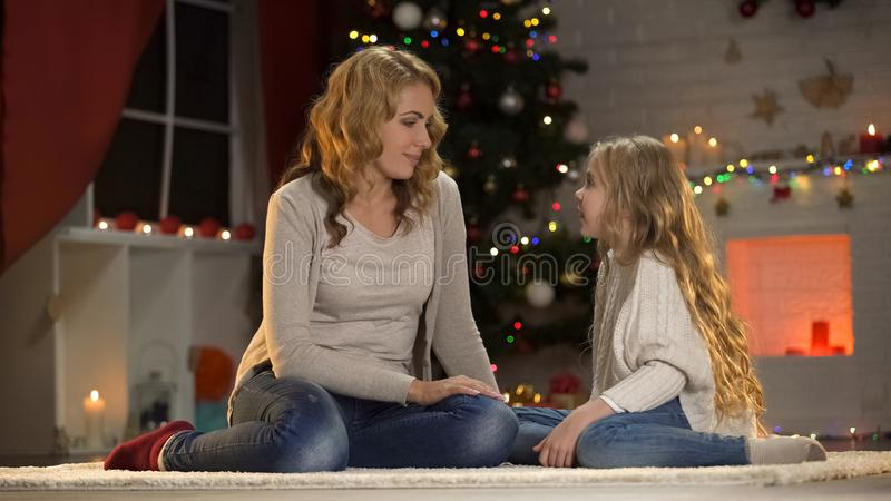 Mother and little daughter communicating on Christmas, waiting Santa together. Stock photo royalty free stock image