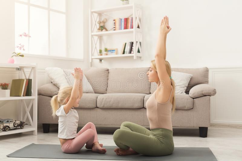 Mother and little daughter doing yoga together stock photography