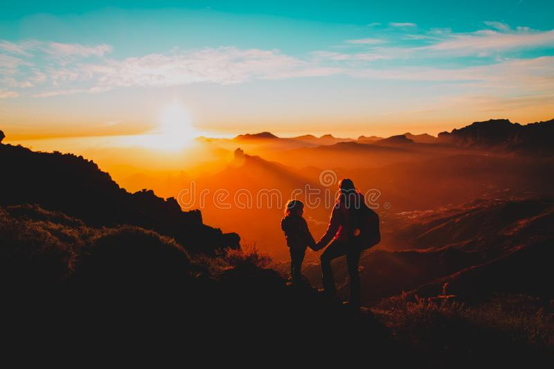 Mother with little daughter enjoy travel in sunset mountains royalty free stock images