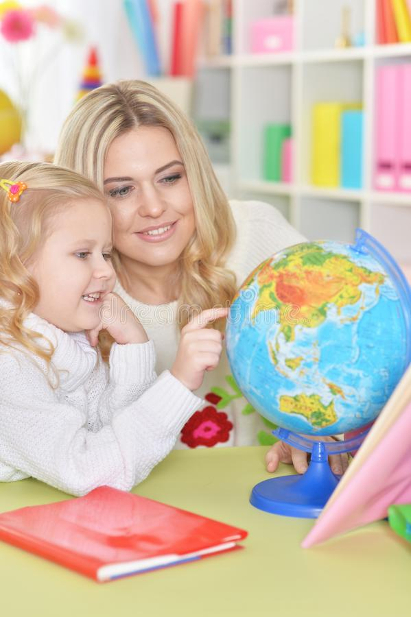 Portrait of mother with little daughter examine globe. Mother with little daughter examine globe at home stock image