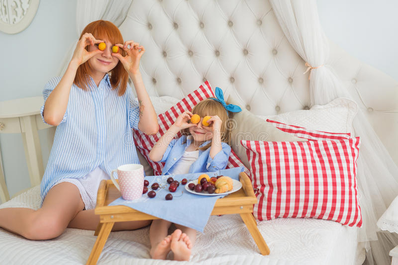 Mother and little daughter fun at breakfast on a bed stock image