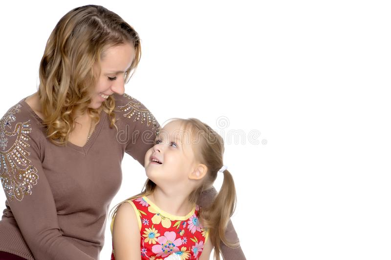 Mother and little daughter gently embrace stock photography