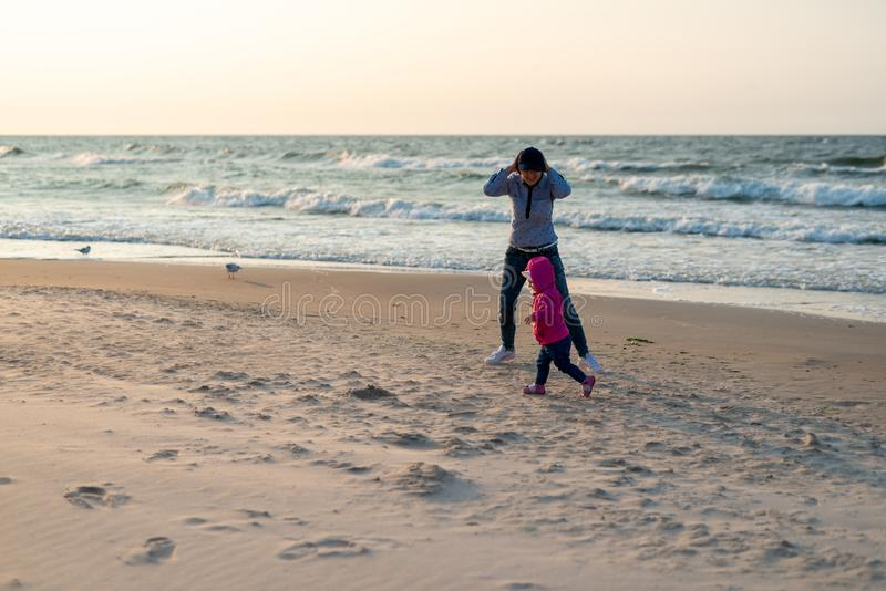 Mother and little daughter having fun on the beach. Authentic lifestyle image royalty free stock image