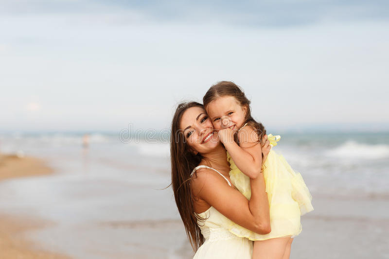 Mother and little daughter are having fun on the beach royalty free stock photography