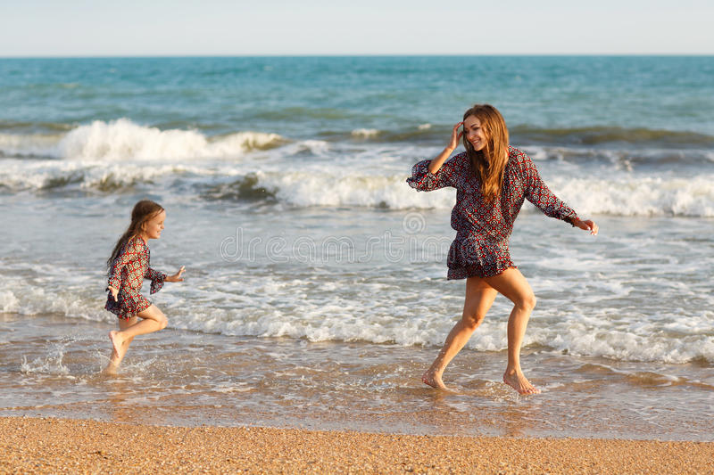 Mother and little daughter are having fun on the beach stock photography