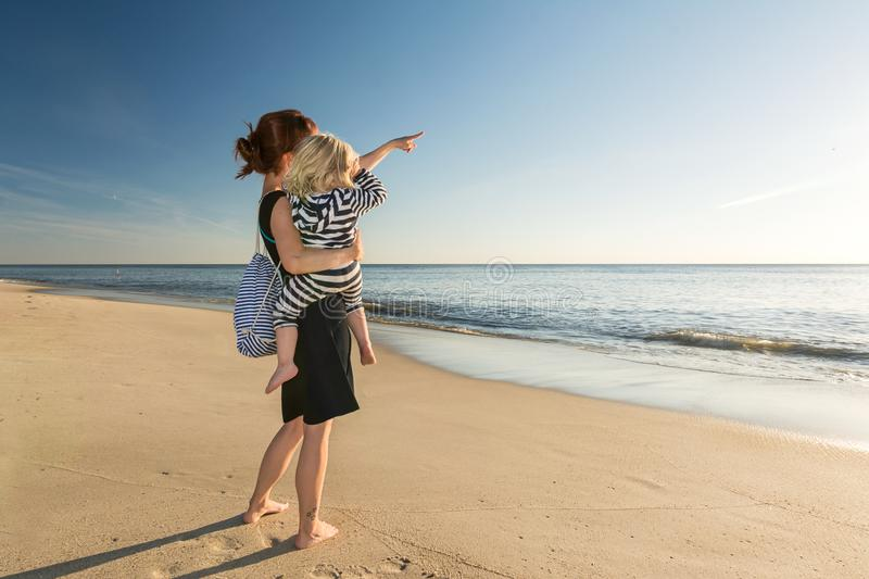 Mother with little daughter on her arm at the beach royalty free stock photos
