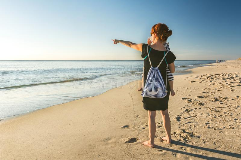 Mother with little daughter on her arm at the beach pointing towards the ocean stock photography