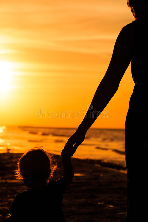 Mother and little daughter holding hands at sunset. Mother and little daughter holding hands on beach at sunset stock images
