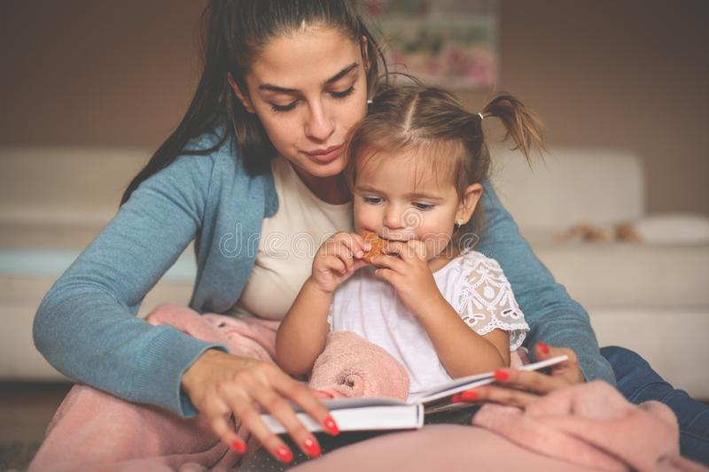 Mother and little daughter at home reading book and little stock photo