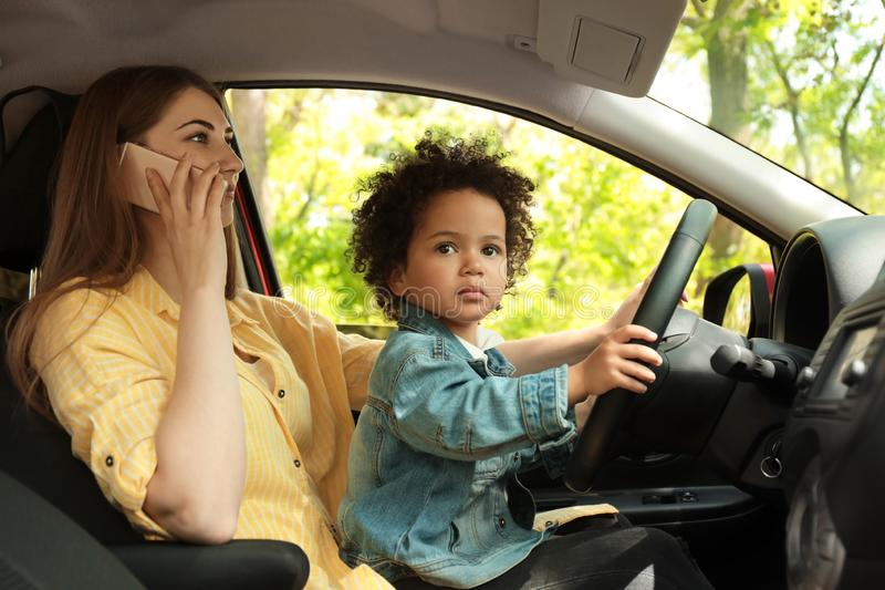 Mother with little daughter on knees driving car and talking by phone stock image