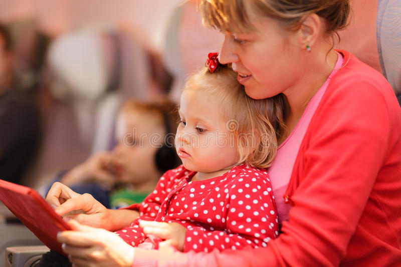 Mother and little daughter looking at touch pad in royalty free stock photos