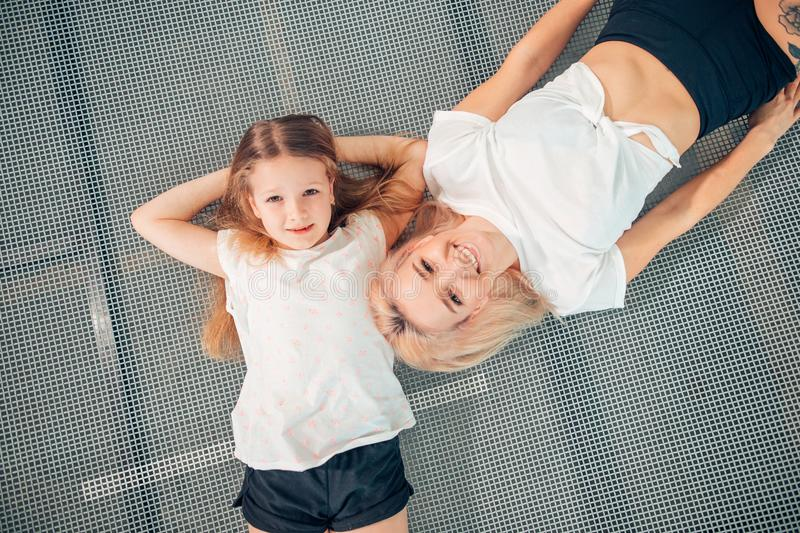Mother and little daughter playing at playground and lying on trampoline stock photos