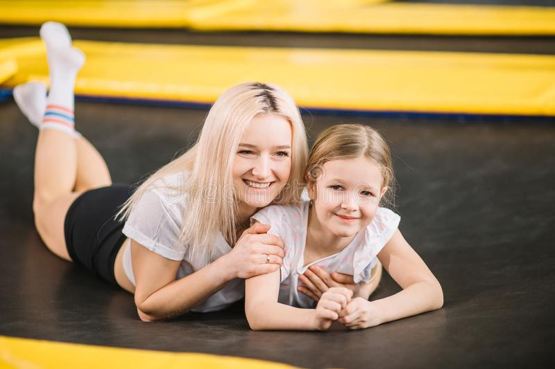 Mother and little girl playing at playground and lying on a trampoline royalty free stock photo