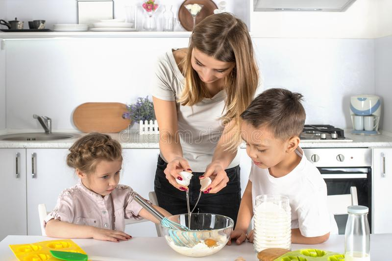 Mother with the little daughter and the son do together dough in. Kitchen. Mother breaks egg in dough, and children observe with interest stock photography