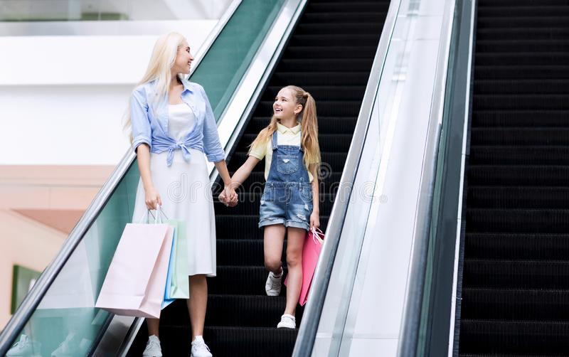 Mother And Little Daughter Standing On Escalator Shopping In Hypermarket. Cheerful Mother And Little Daughter Doing Shopping Standing On Escalator Moving Stairs stock photos