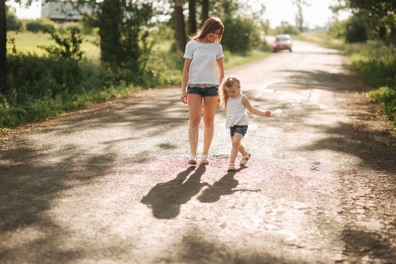 Mother and little daughter walk though the alley and hold each others hands. Shadow on the road royalty free stock images