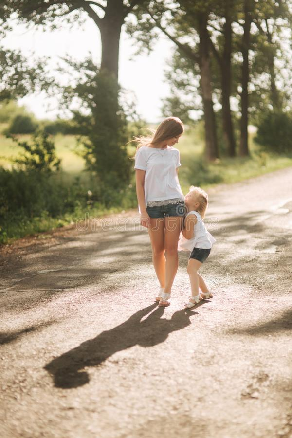 Mother and little daughter walk though the alley and hold each others hands. Shadow on the road stock photography