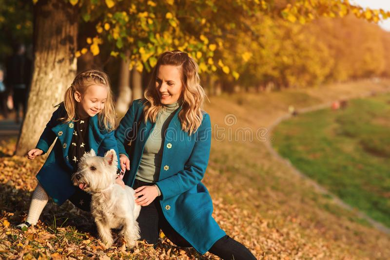 Mother and little daughter walking with dog in autumn. Outdoors portrait of happy family. Autumn fashion. Stylish little daughter stock photography