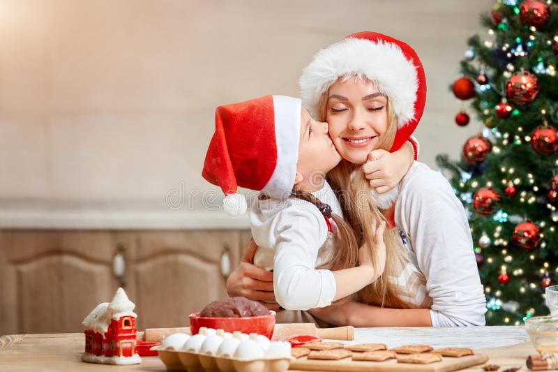 Mother and little girl baking Christmas pastry. Children bake gingerbread. royalty free stock photos