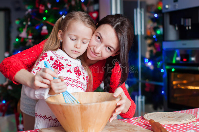 Mother and little girl baking Christmas pastry. Mom and little girl baking Christmas pastry. Children bake gingerbread stock photography