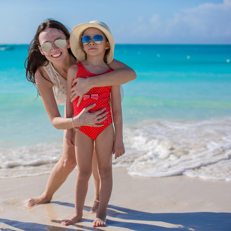 Mother and little girl at beach on sunny day stock image
