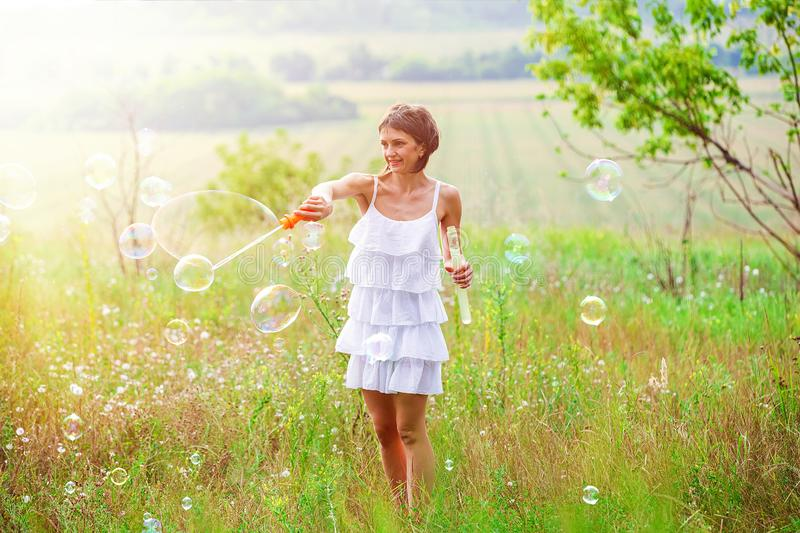Mother and little girl daughter child blowing soap bubbles outdoor. Parent and kid having fun on meadow. Happy and stock photos