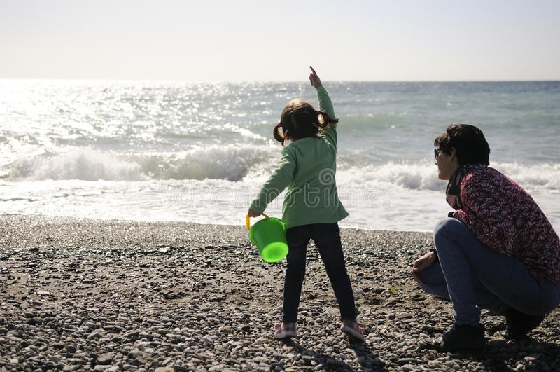 Mother and little girl having fun on the beach in winter royalty free stock photo