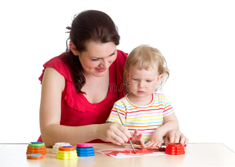 Mother and little girl paint together at home stock photography