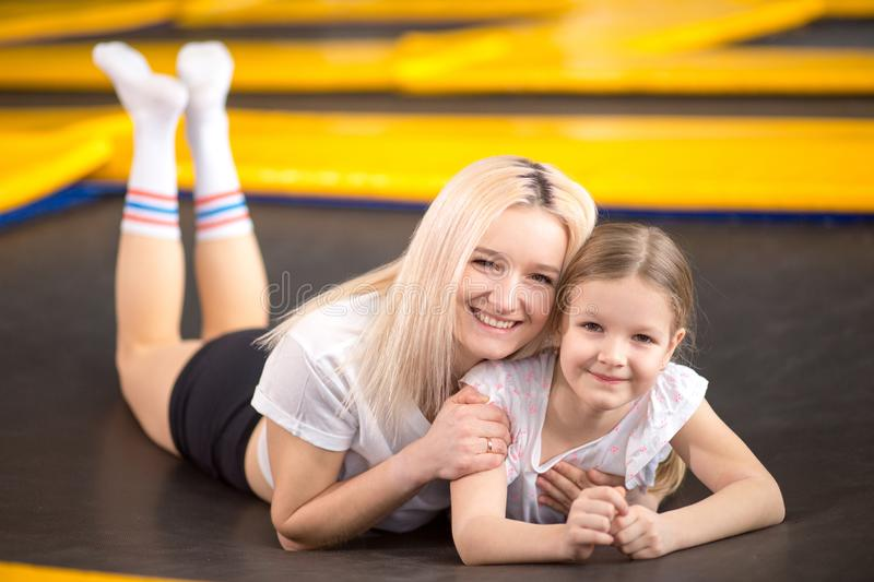 Mother and little girl playing at playground and lying on a trampoline royalty free stock photos