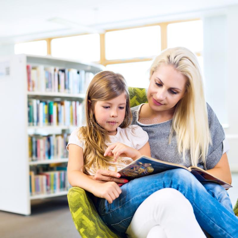 Mother with little girl read book together in library. Happy family, preschool concept. Parent educating children stock photography