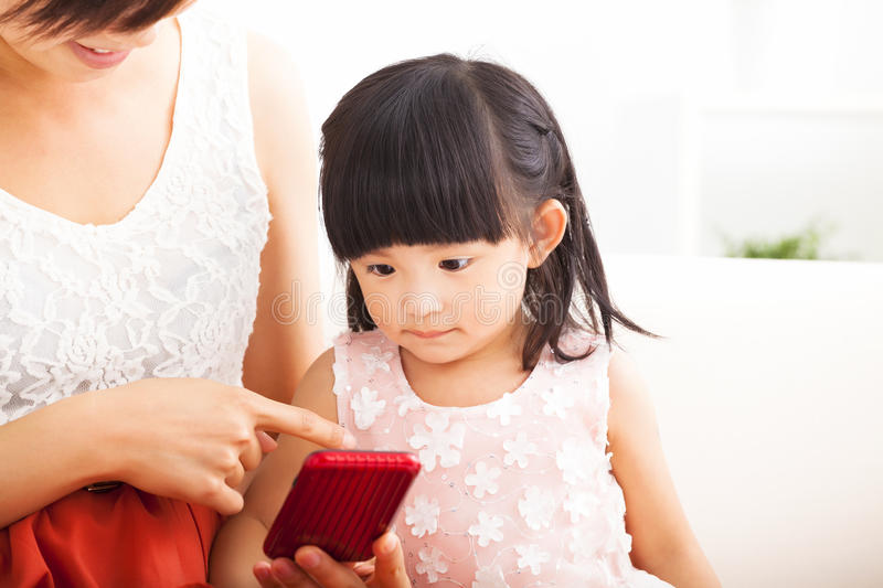 Mother and little girl using smartphone together stock image