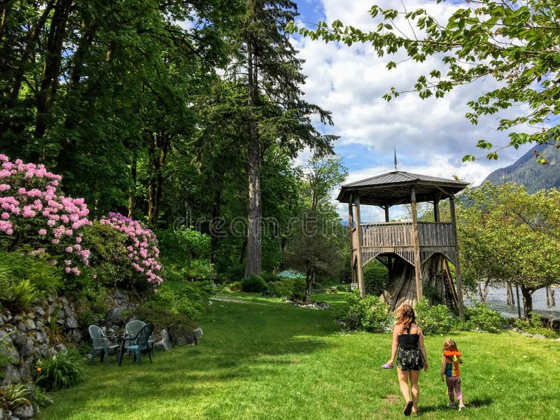 A mother and little girl walking towards a beautiful wooden pagoda on top of a tree stump surrounded by pink flowers. And tall evergreen trees in a remote stock image