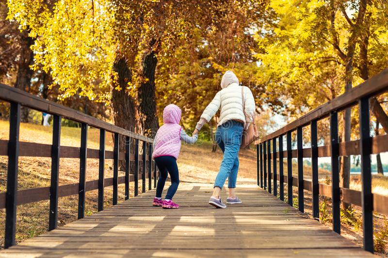 Mother and little preschooler daughter having fun and fooling around in autumn city park. Mom and child walking and jumping on stock images