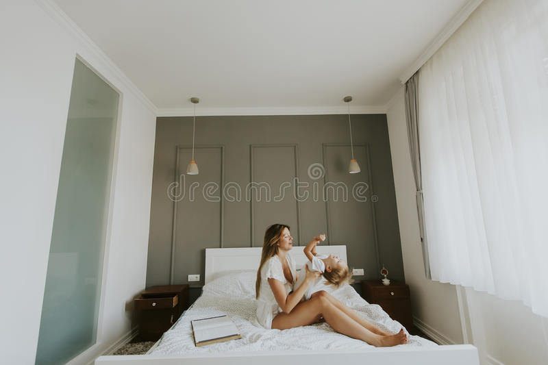 Mother and little son having fun in bed royalty free stock image