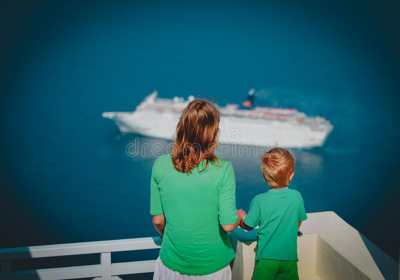 Mother and little son looking at cruise ship at sea, Santorini, Greece stock image